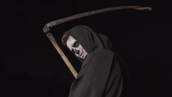 Rear View of Creepy Grim Reaper Walking Into Darkness