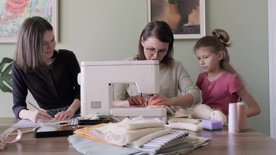 Thumbnail for Mother and Two Daughters Sewing Together Toy on Sewing Machine at Home