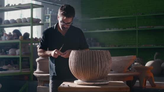 Male Ceramist Crafting Striped Clay Vessel