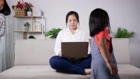 Mom concentrate on working with laptop and kids are mischievous