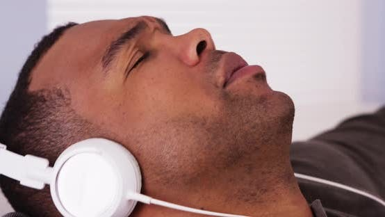 Thumbnail for Black man listening to music with headphones