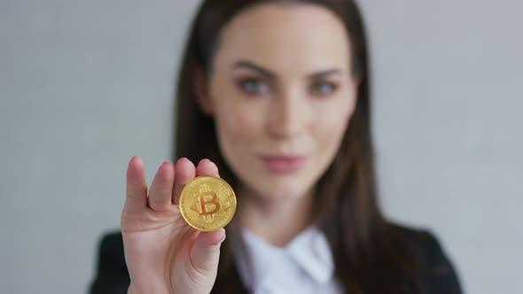 Thumbnail for Ziemlich junge Frau in schwarz Jacke Demonstration Bitcoin und Blick auf Kamera