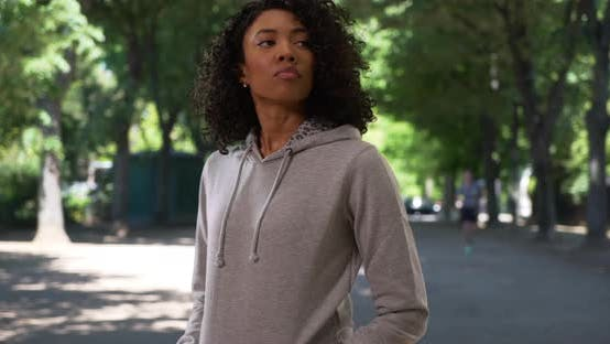 Thumbnail for African American woman in grey hoodie waiting for friend in public park