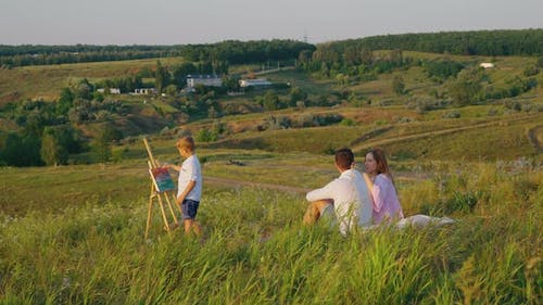 Family Relaxing on Hill and Boy Painting on Easel