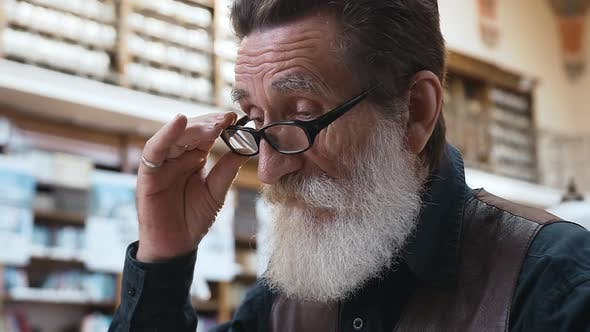 Thumbnail for Serious Senior Bearded Man with Eyeglasses which Reading in the Library