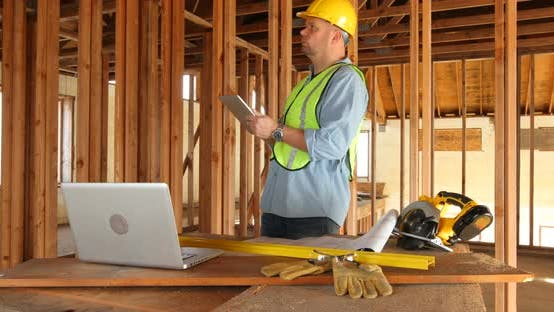 Thumbnail for Construction worker using digital tablet and laptop computer