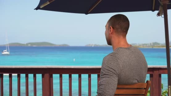 Thumbnail for Black man on vacation sitting on deck looking over ocean view