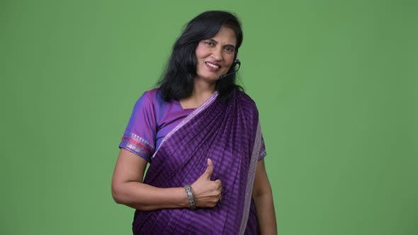 Thumbnail for Mature Happy Beautiful Indian Woman As Call Center Representative Smiling While Giving Thumbs Up