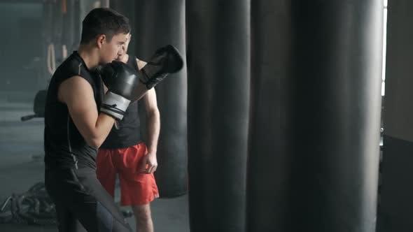 Boxer und sein Coach üben einige Moves auf einem Boxsack in einem Fitnessstudio. 50fps Footage