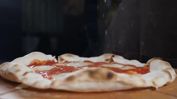 Thumbnail for Close-up of Chef Pouring Seasonings on Baked Cooked Readymade Pizza at Italian Restaurant Kitchen in