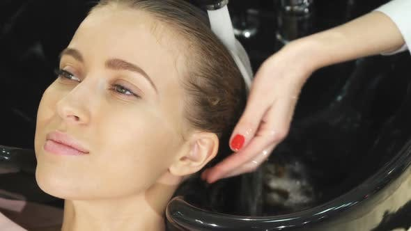 Thumbnail for Top View Close Up of a Woman Smiling While Getting Her Hair Washed By a Hairdresser