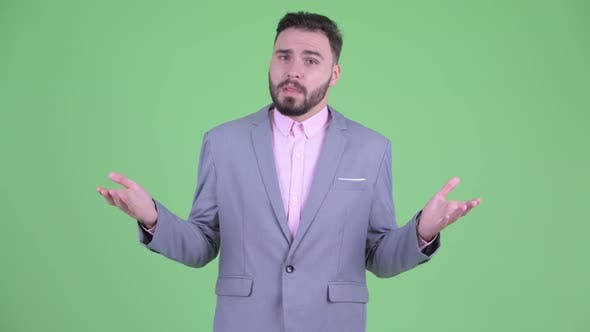 Thumbnail for Confused Young Bearded Businessman Shrugging Shoulders