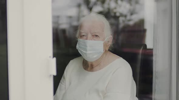 Portrait Of Old Woman In Medical Mask. Woman Looking Out The Window