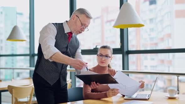 Mature entrepreneur explaining the work to a secretary