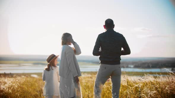 Thumbnail for Young Family with Little Baby and Girl Standing on the Field and Looking Into the Distance - the
