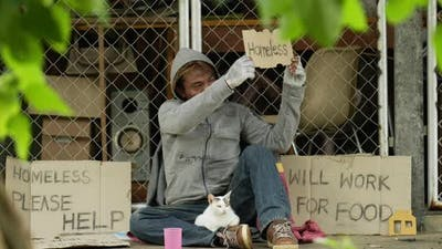 Homeless with dirty clothes holding homeless label