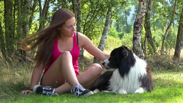 Thumbnail for A Young Woman and a Border Collie Lie on Grass in a Meadow, the Woman Pets the Dog and Smiles