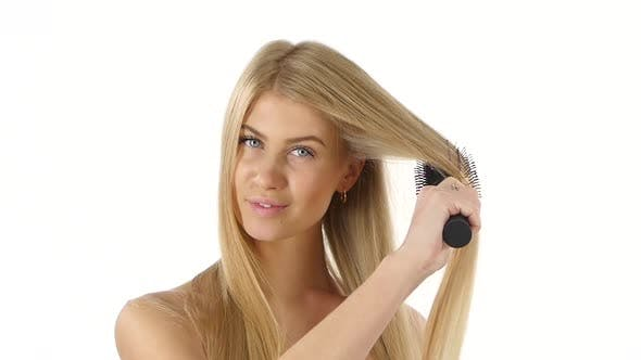Beautiful Blond Brushing Her Hair. Slow Motion, Bathroom