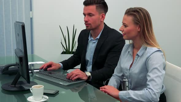 Thumbnail for A Man and a Woman Sit at a Desk in Office, He Works on a Computer, She Talks, Then Smiles To Camera