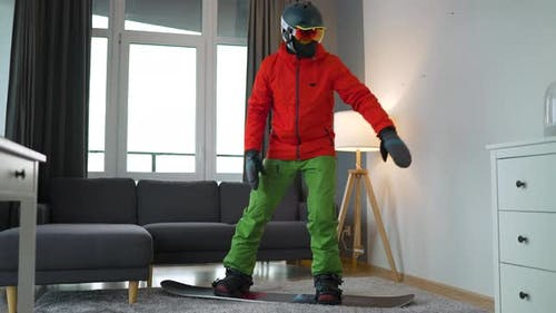 Snowboarder depicts snowboarding on a carpet in a cozy room