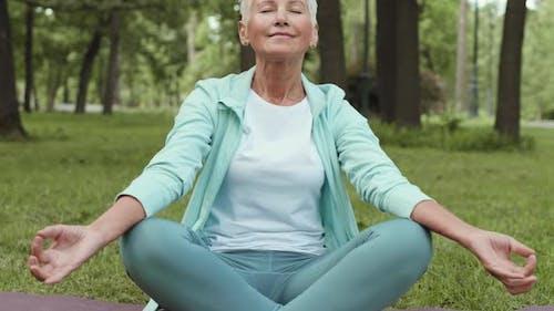 Portrait of Old Female Yogi Meditating in Park