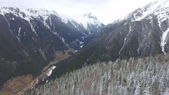 Thumbnail for Fly Over a Large Snowy Forested Valley