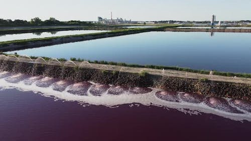 Aerial view of a red-colored wastewater reservoir near an industrial plant.