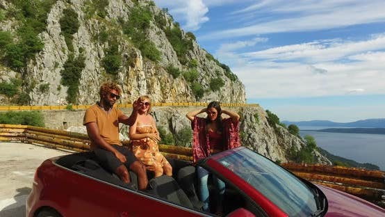 Thumbnail for Multi ethnic friends partying in red convertible parked on side of coastal road
