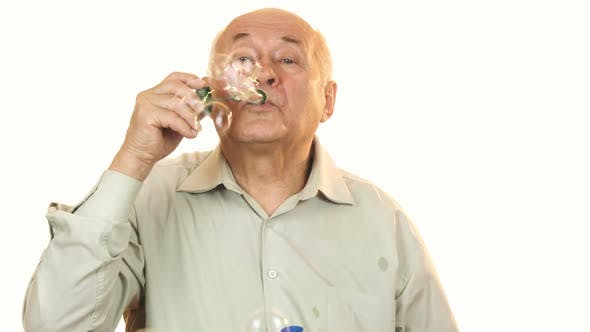 Thumbnail for Senior Cheerful Man Blowing Bubbles Isolated on White