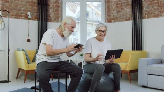 Thumbnail for Senior Couple Enjoying Revisions Phone and Tablet Apps while Relaxing