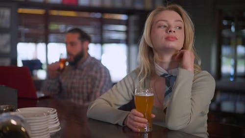 Portrait of Charming Young Slim Woman Sitting at Bar Counter with Beer Pint As Man Drinking at