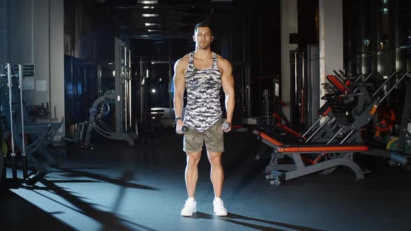 Thumbnail for Athletic Sportsman Works Out and Lifts Hands With Dumbbells Gym