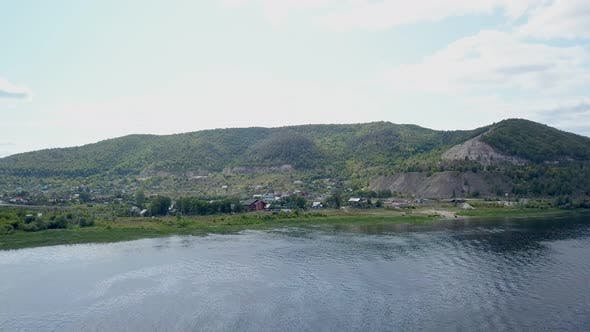 Thumbnail for Calm Aerial View on Coast of River with Hills, Small Village