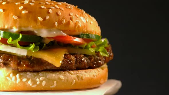 Thumbnail for Big appetizing burger with meat cutlet. Isolated hamburger on dark smoke background, close-up view
