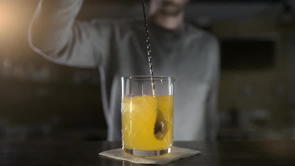 Thumbnail for Bartender Mixes Cocktail Ingredients with Long Bar Spoon in Slow Motion, Fresh Drinks in the Bar
