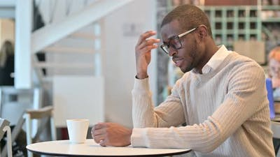 Concerned African Man Thinking in Cafe, Worrying