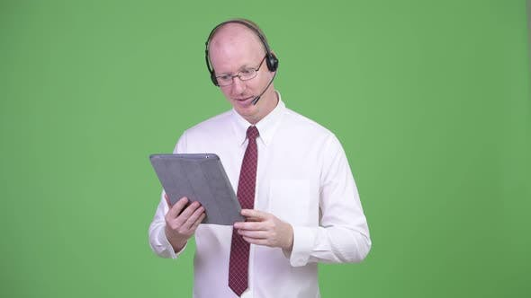 Thumbnail for Happy Mature Bald Businessman Working As Call Center Representative