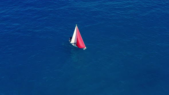 Thumbnail for Aerial View. Sailing Yacht with Red Sail in the Open Sea.