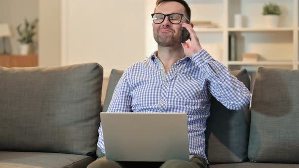 Thumbnail for Cheerful Man with Laptop Talking on Smartphone