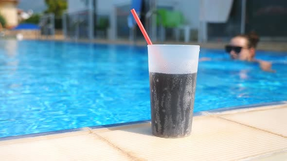 Thumbnail for Close Up Glass of Cool Cocktail Standing on Edge of Pool. Young Girl in Sunglasses Swimming at