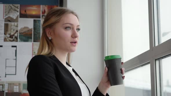 Smart Young Businesswoman Having Coffee Break in Office