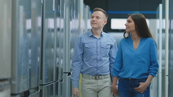 Thumbnail for A Young Couple, a Man and a Woman Choose a New Fridge. They Open the Door and Look at the