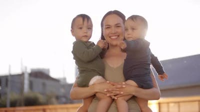 Happy Asian Mom Posing with Twin Babies Outdoors in Sun