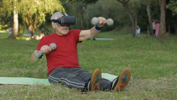 Thumbnail for Senior Old Grandfather Man in VR Headset Helmet Making Fitness Exercises with Dumbbells in Park