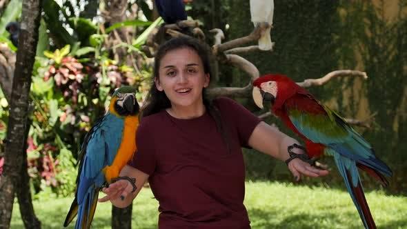 Thumbnail for Femme caucasienne est photographié comme un souvenir avec deux perroquets Ara