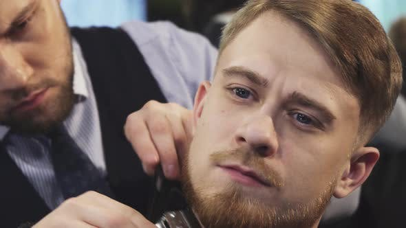 Thumbnail for Professional Barber Trimming Beard of a Young Man