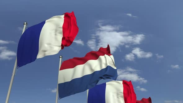 Flags of Netherlands and France Against Blue Sky