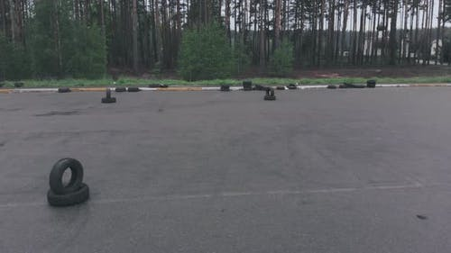 Empty asphalt autodrome with road markings and tires. Driving lessons training at car parking