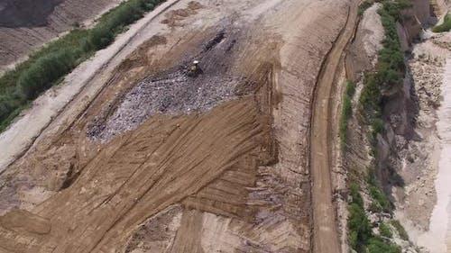 Digger Moves Garbage in Junkyard
