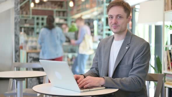 Thumbs Up By Young Man with Laptop in Cafe